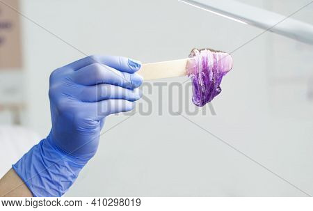 A Girl Beautician Holds A Sugar Paste For Epilation On A Spatula Under The Light Of A Paw. Spatula A