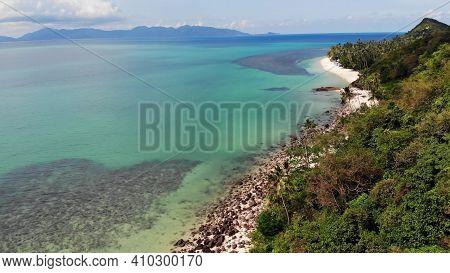Green Jungle And Stony Beach Near Sea. Tropical Rainforest And Rocks Near Calm Blue Sea On White San