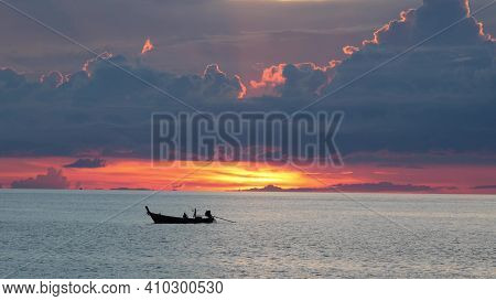Boat In Sea During Sunset. Silhouette Of Small Rowing Boat Floating On Rippling Water Of Calm Sea Du