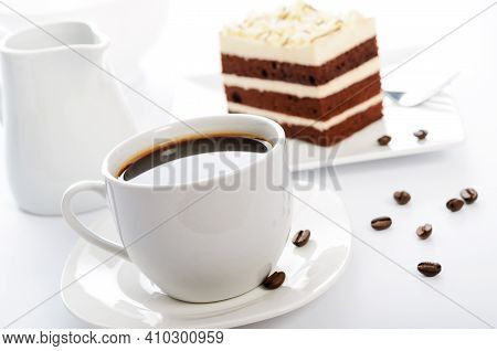 White Cup Of Coffee With Cocoa Sponge Cake On A Saucer And Scattered Coffee Beans In Close-up
