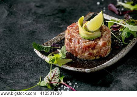 Tuna Tartare With Green Salad, Lime, Avocado And Mustard Sauce Serving On Japanese Style Black Ceram