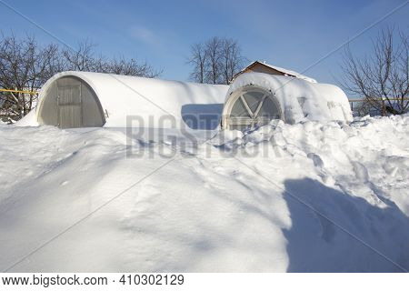 Greenhouses In The Snow. There Is A Lot Of Snow In The Garden. Winter Day In The Village. Winter In