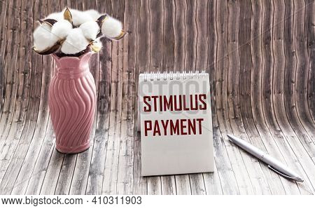 The Stimulus Payment Incentive Is Written In A Notepad On A Wooden Table Next To A Vase With A Cotto