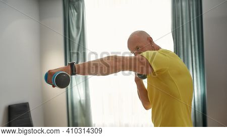 Strong Trainer With Dumbbells In Hand Working Out At Home. Male Trainer Boxing With A Dumbbell In Hi