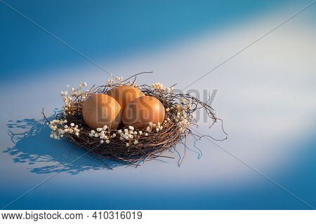 Easter Basket And Spring Flowers With Easter Eggs On Wooden Background With Morning Sunny Window Lig
