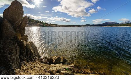 Landscape Of Lake And Rocks With The Sun Through The Clouds, Blue Sky And Reflections In The Water.