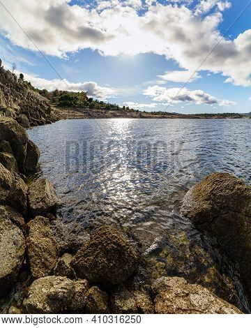 Landscape Of Rocks In A Blue Lake With Sky With Clouds And Sun Reflecting In The Water.
