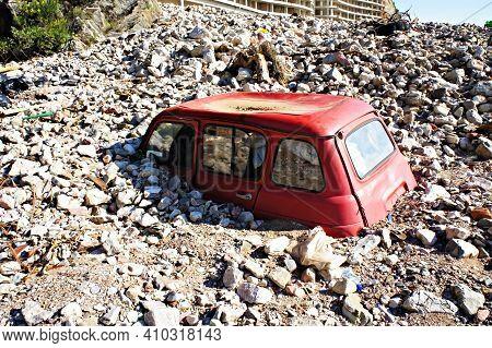 Abandoned Old Red Rusty Car In A Junkyard Buried In Stones, Scrapyard, Scrap Metal