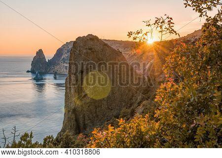 Autumn Sea Landscape With Warm Sunset Light Over Rocky Coastline. Calm Sea On A Background Of Rocky