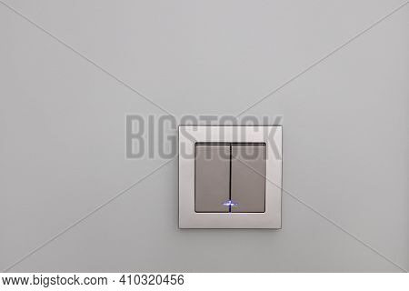 Fashionable Modern Silver Light Switches On A Gray Wall, Opposite View. Switch With Night Illuminati
