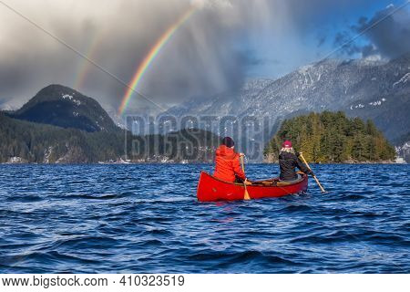 Couple Friends On A Wooden Canoe Are Paddling In Water. Dramatic Rainbow Sky Art Render. Taken In In