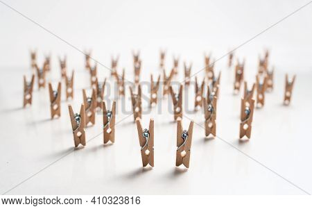 Many Small Wooden Clothespins Stand On A White Background. Clothespins Are Like A Crowd Of People Wi