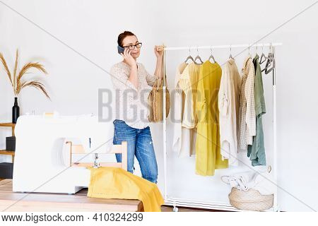 Seamstress Makes The Phone Call In Front Of The Sewing Machine In Small Fashion Studio. Fashion Atel