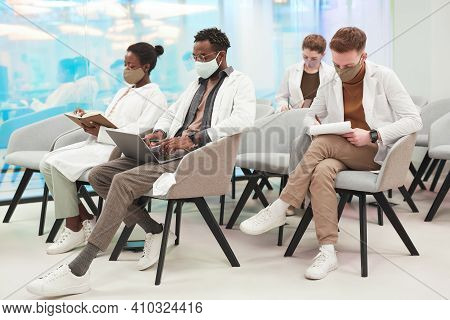Side View At Multi-ethnic Group Of People Wearing Masks And Lab Coats While Listening To Lecture On