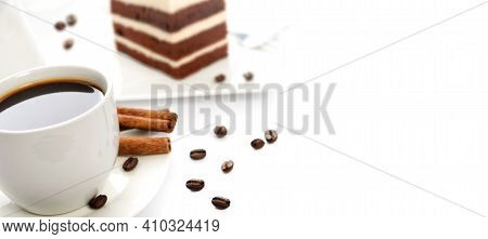 White Cup Of Coffee With Cinnamon Sticks, Cocoa Sponge Cake On A Saucer And Scattered Coffee Beans I