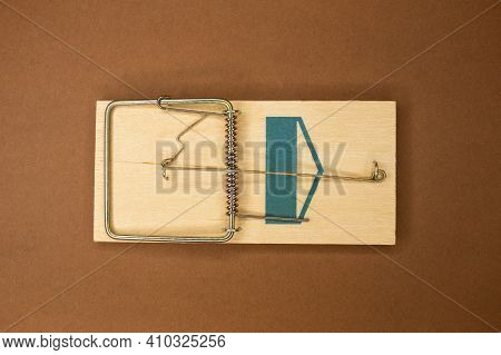 Wooden Mousetrap On A Brown Background. Concept: Danger Deception
