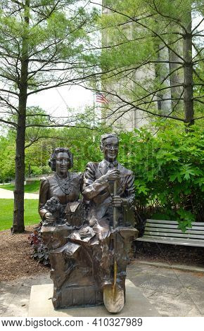 NAPERVILLE, ILLINOIS - MAY 26, 2017: Mr and Mrs Naperville Statue. The tribute to Margaret and Harold Moser is in the citys Riverwalk. Moser Tower and Millennium Carillon are in the background.