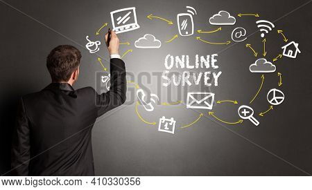 businessman drawing social media icons with ONLINE SURVEY inscription, new media concept