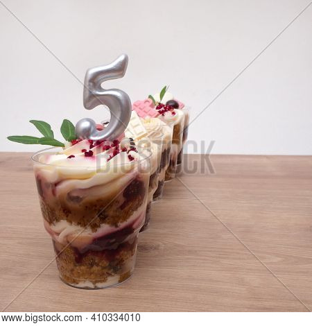 Birthday Trifle Cake With Candle Labeled Number 5. Five Portioned Mini Cakes.