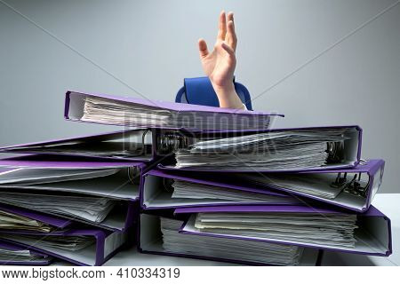 Raised Hands Of A Person Who Sinks Behind Stacks Of Ring Binders On An Office Desk. Concept Of Exces