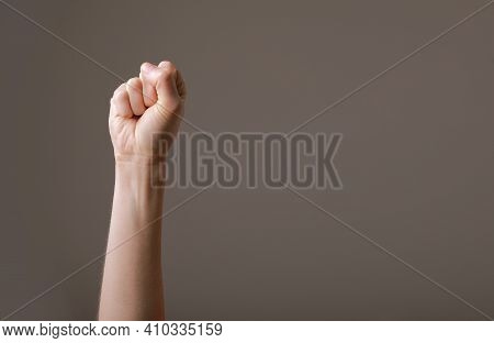 Female Hand Clenched Into A Fist On A Gray Background. Gesture Of Fighting, Winning Or Protest. Huma