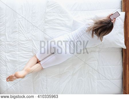 Woman Lying On Her Stomach In Bed And Looking At Phone Tip View. Insomnia Concept