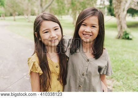 Happy And Healthy Mixed Asian Young Girls  Smiling In The Park, Best Friends And Friendship And Dive