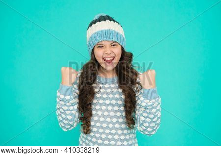 Happy Kid In Warm Sweater Selebrate Success. Keep Head In Warmth. Cozy And Comfortable. Best Winter