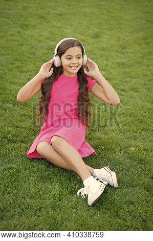 Headphones Protecting Sensitive Ears. Happy Baby Wear Headphones On Green Grass. Small Child Listen