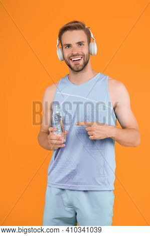 Stay Hydrated When Training. Happy Guy Point Finger At Water Bottle. Thirsty Athlete In Sportswear.