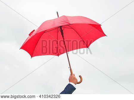 Man's Hand Holds Red Open Umbrella Against Light Sky.