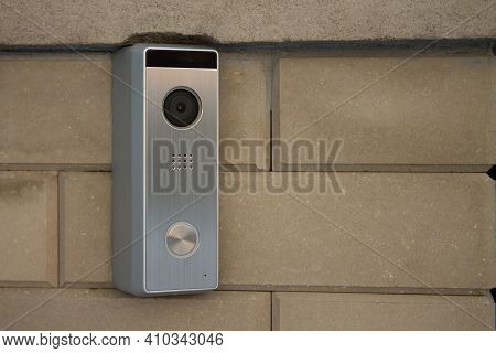 Silver Intercom Panel With Video Camera, On A Brick Beige Fence Pillar Of A Private House