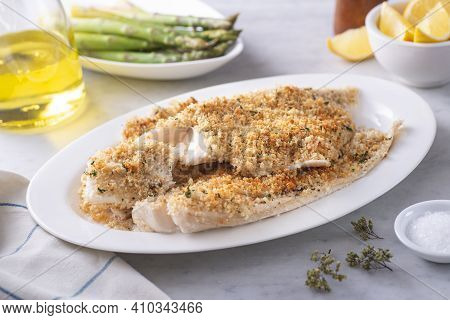A Plate Of Delicious Panko Breadcrumb Crusted Baked Haddock With Asparagus And Lemon.