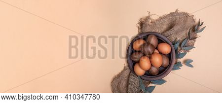 Clay Plate Full Of Painted Eastr Eggs On Sustainable Burlap Cloth