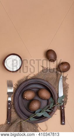Vertical Banner With Ceramic Plate On Burlap Cloth With Easter Eggs, Cream Bowl And Eucalyptus Branc