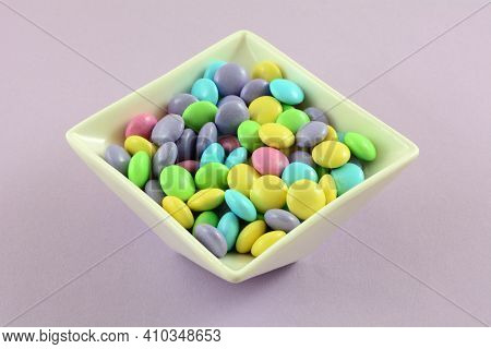 Pastel Easter Candy Coated Milk Chocolate Candy Pieces In White Candy Dish On Lavender Background