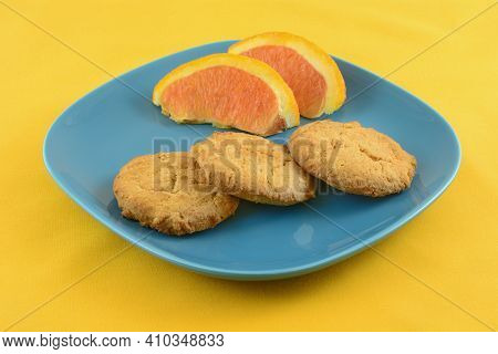 Orange Zest Butter Cookies With Orange Slices On Blue Snack Plate On Yellow Tablecloth