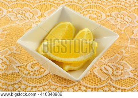 Fresh Raw Lemon Slices In White Ingredient Bowl On White Lace On Yellow Tablecloth