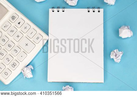 A Notebook With A White Blank Sheet On A Blue Background Among Crumpled Sheets Of Paper And Next To