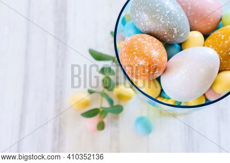 Easter Sweets And Pastel Colored Eggs In A Beautiful Glass Vase. Easter Celebration Concept. Top Vie