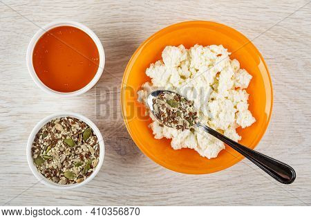 White Bowl With Liquid Honey, Bowl With Mix Of Different Seeds, Teaspoon With Mix Of Different Seeds
