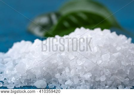 Coarse Salt Crystals On A Blue Table. Sea Salt. Background For Advertising Salty.