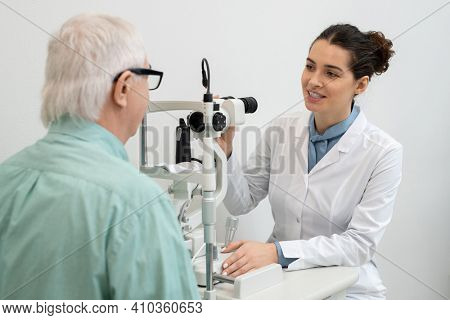 Young pretty female ophthalmologist in whitecoat sitting by medical equipment in clinics and going to test eyesight of senior male patient