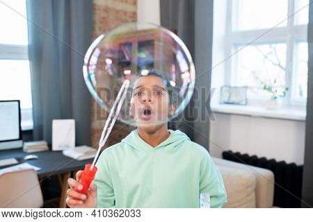 Cute girl of elementary age in casualwear blowing huge soap bubble while standing in front of camera and having fun in home environment