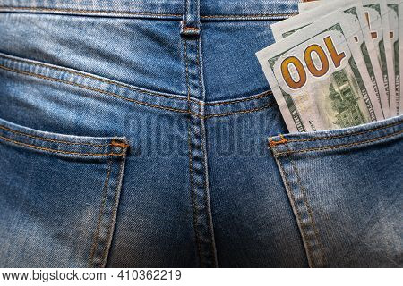 Cash In Your Pocket. A Hundred Dollar Bills Stuck Out Of The Back Pocket Of Blue Jeans. Money Saving