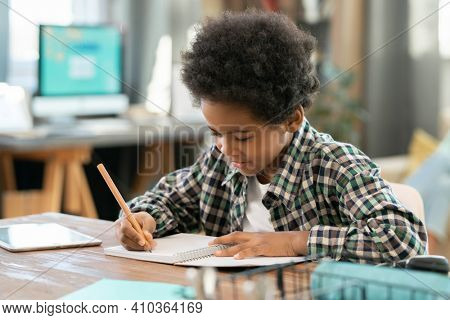 Elementary schoolboy of African ethnicity making notes in copybook while doing homework by table in living-room against computer