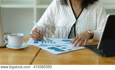 Female Office Worker Analysing Business Document On Wooden Worktable