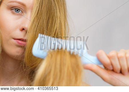 Blonde Girl Combing Her Long Messy Hair