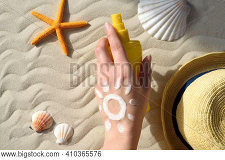 Hand With Sunscreen. Seashells, Starfish, Sun Hat, Sunscreen And Hand With Cream. The Concept Of Pro