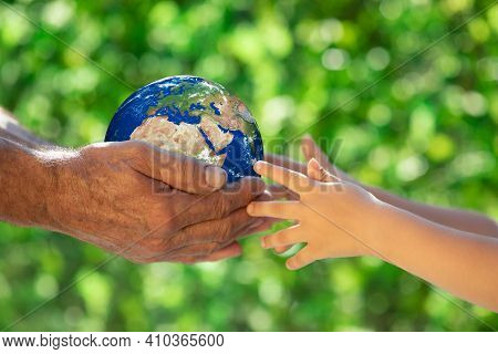 Family Holding 3d Planet In Hands Against Green Blurred Background. Earth Day Spring Holiday Concept